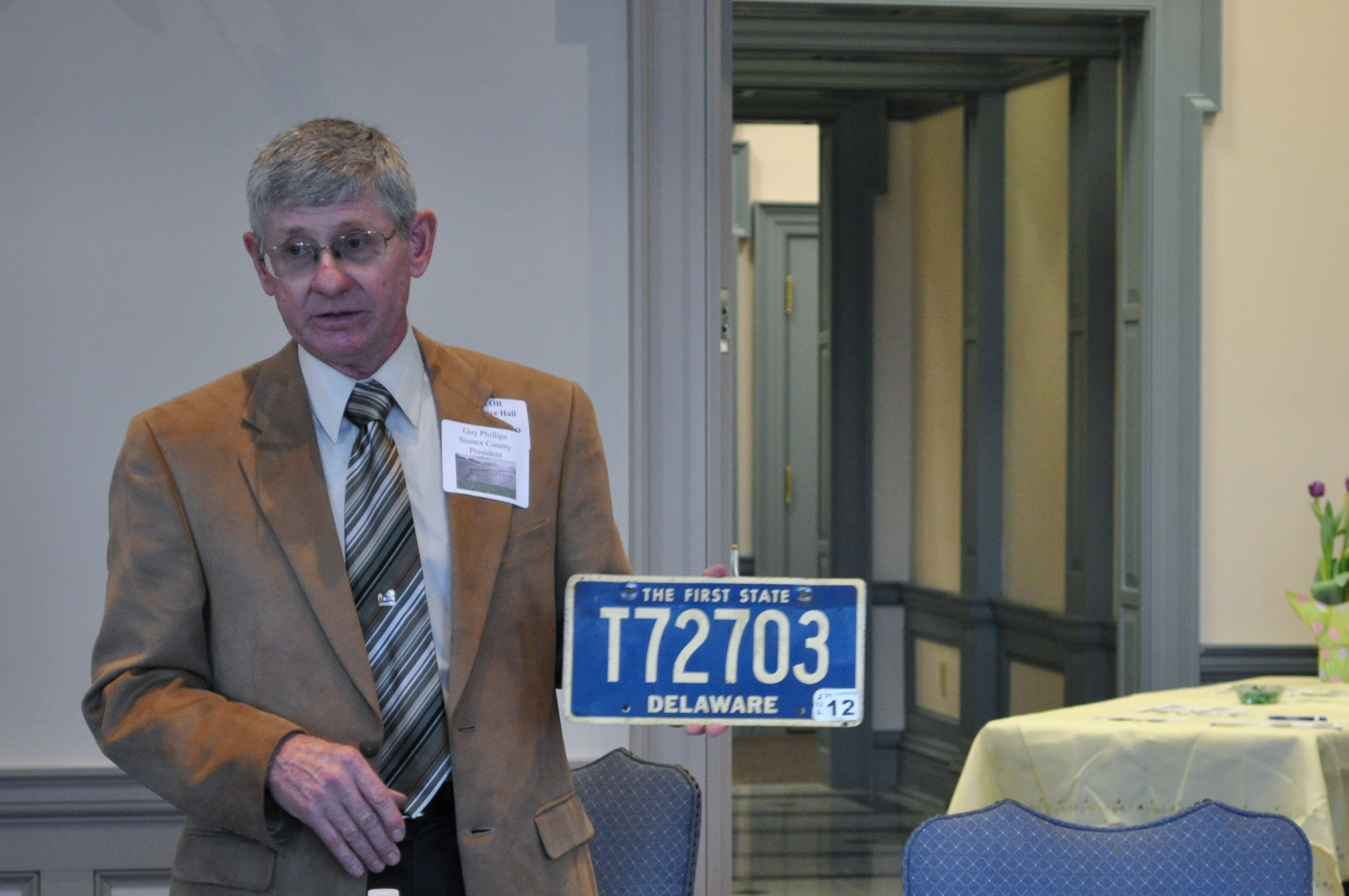 Guy Phillips, Sussex County Farm Bureau President, shows guests a Delaware trailer tag at Tuesday's Legislative Luncheon.